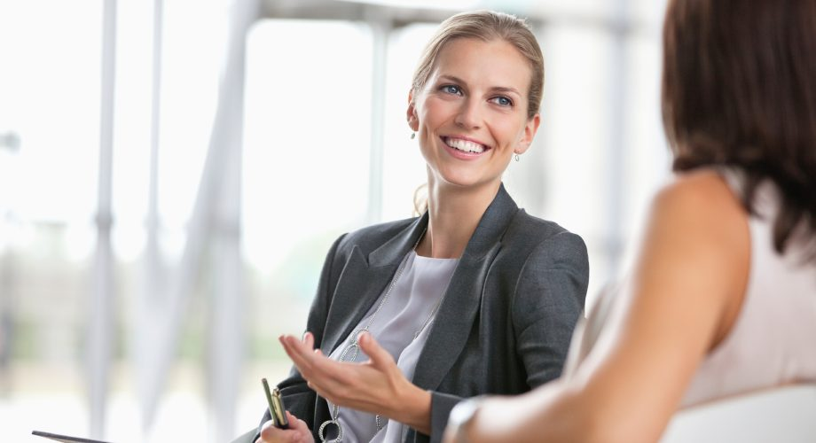Two young businesswomen chatting with each other at office cafeteria